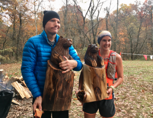 Photo by Kevin Spradlin Brad Hinton and Michelle Benshoff pose with their hard-earned bear carvings, presented to the top male and female finisher of the 2017 Fire on the Mountain 50K trail race in Green Ridge State Forest.